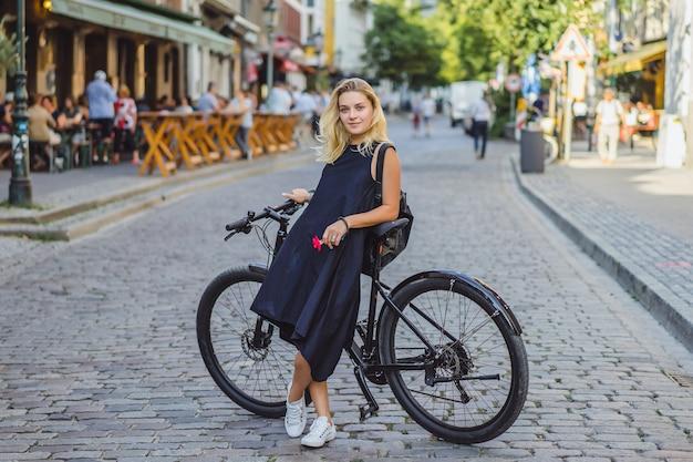 ヨーロッパの都市で自転車に乗る若いスポーツ女性。都市環境におけるスポーツ 無料写真