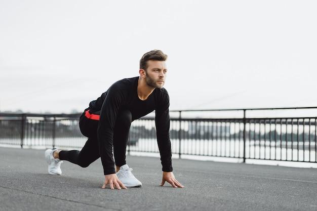 ヨーロッパの都市でスポーツをしている若い男。都市環境におけるスポーツ 無料写真