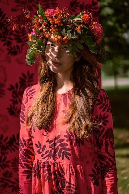 リネンのドレスの少女。彼女の頭に花の花輪を捧げる。 無料写真
