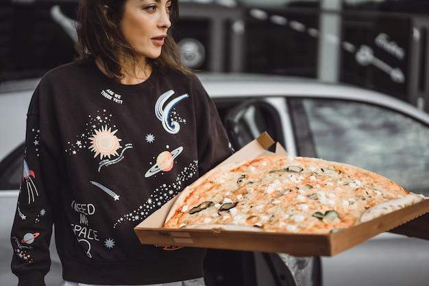 街のピザのスライスを食べる若い美しい女性 無料写真