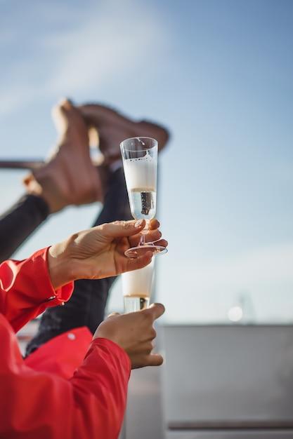 ヨットの上でシャンパンを飲む赤いマントの美しい若い女性。 無料写真