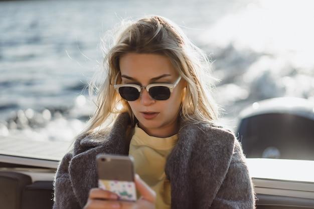 スマートフォンで写真を撮る美しい若い女性 無料写真