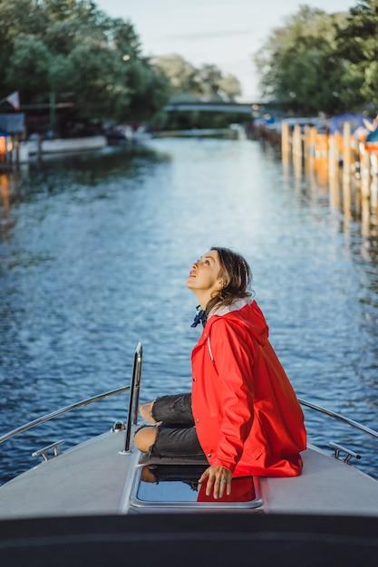 赤いレインコートを着た美しい若い女性は、プライベートヨットに乗る。スウェーデンのストックホルム 無料写真