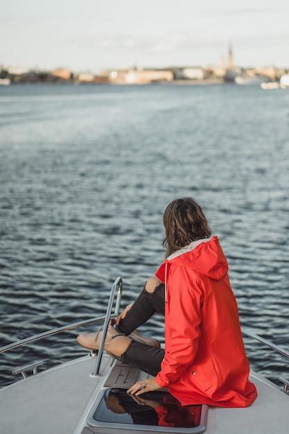 Красивая молодая женщина в красном плаще едет на частной яхте. стокгольм, швеция Бесплатные Фотографии