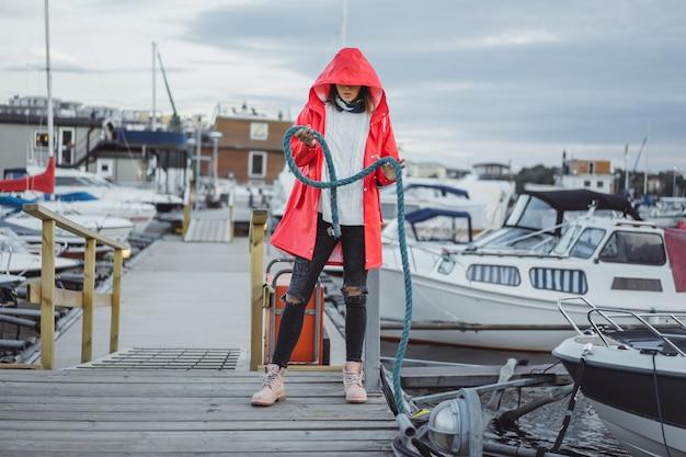 ヨット港の赤いマントの美しい若い女性。スウェーデンのストックホルム 無料写真