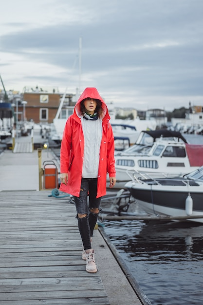 Красивая молодая женщина в красном плаще в порту яхты. стокгольм, швеция Бесплатные Фотографии