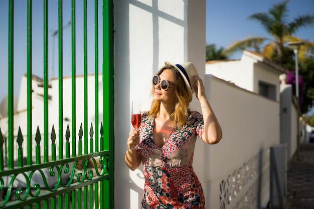 短いドレスを着た若い美しい女性が小さなヨーロッパの町の通りを通って歩きます。夏 無料写真