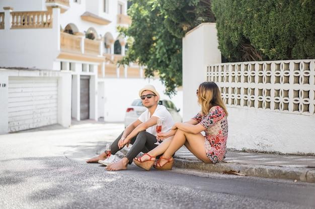 愛の若い幸せなカップルはスペインの小さな通りを歩き、シャンパンを飲み、笑います。休暇 無料写真