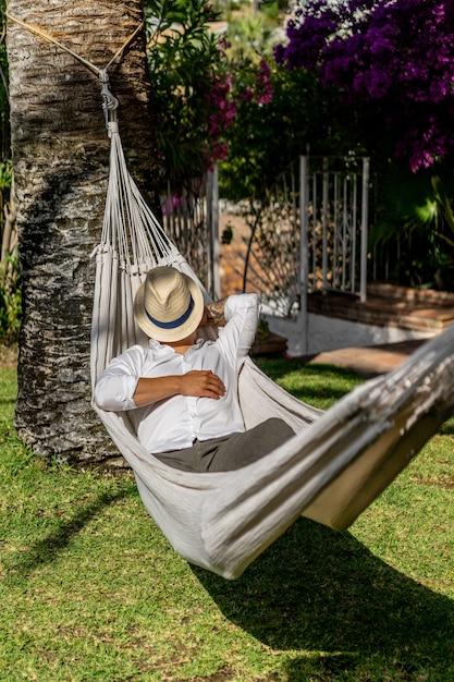 男性が庭でハンモックでリラックス。 無料写真