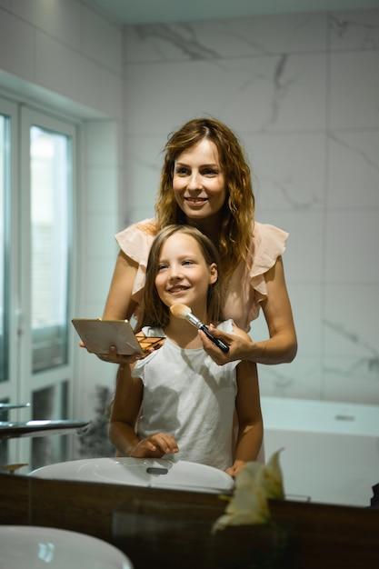 ママと娘はバスルームで化粧をし、鏡の前で口紅を塗る。 無料写真