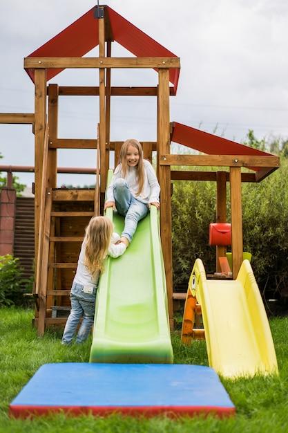 子供たちが子供たちの滑り台から乗る、姉妹たちが庭で一緒に遊ぶ 無料写真