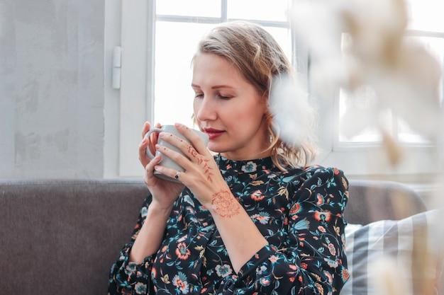 ソファの上に座ってお茶のカップとドレスの美しいロマンチックな若いブロンドの女性 Premium写真