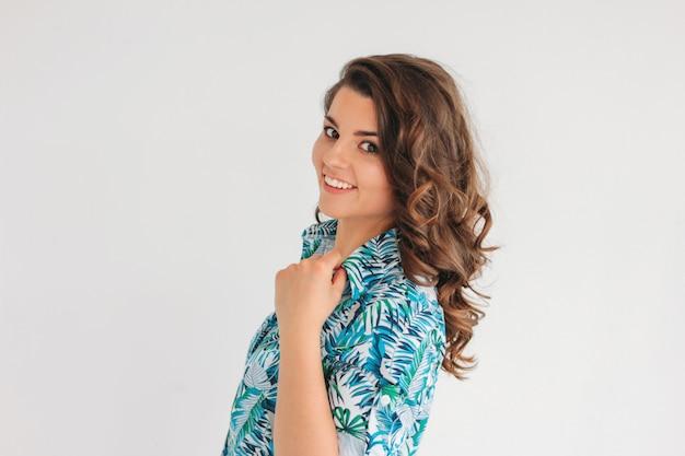 ウェーブのかかった髪の夏のドレスの若い魅力的な笑顔ブルネットの少女は、白で隔離 Premium写真