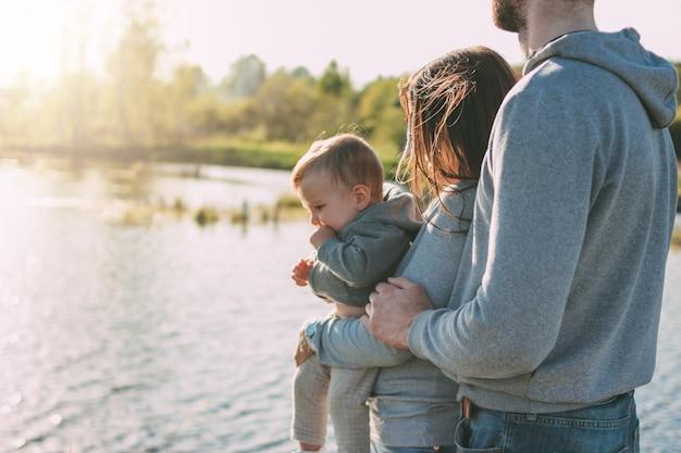 湖でかわいい男の子と幸せな家族 Premium写真