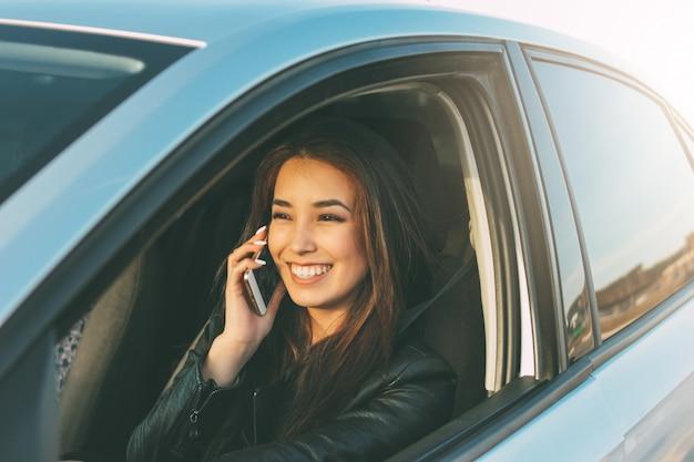 美しいブルネットの長い髪の若いアジア女性運転と携帯電話で話す Premium写真