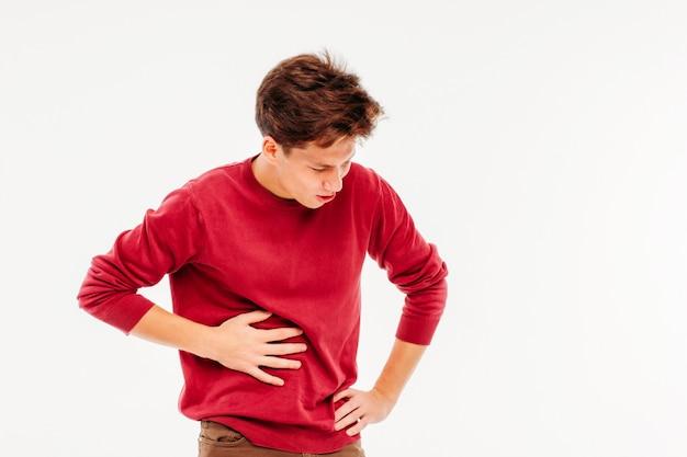 Молодой человек, проведение печени, испытывая боль, на белом фоне Premium Фотографии