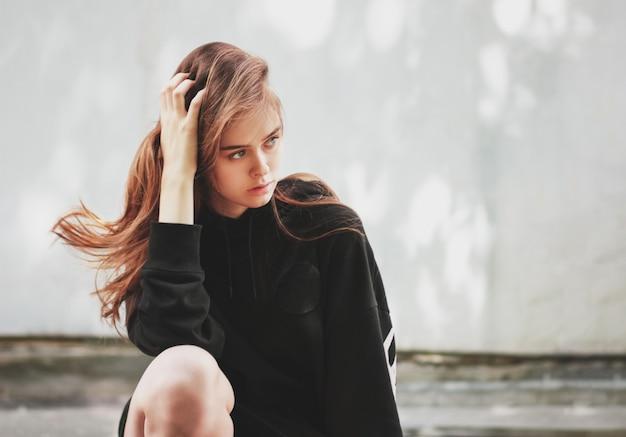 黒のパーカーで若い美しい長い髪の女の子ファッションモデルヒップスターの率直な肖像画 Premium写真