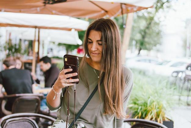 Молодая улыбающаяся длинноволосая брюнетка девушка одела вскользь используя мобильный телефон в уличном кафе Premium Фотографии