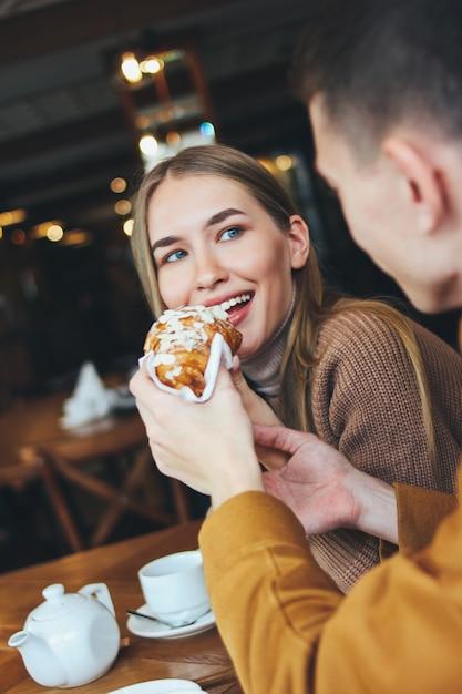 幸せな若いカップルは、一緒にカフェに座って暖かいカジュアルな服を着てください。男は女の子のクロワッサンをフィード Premium写真