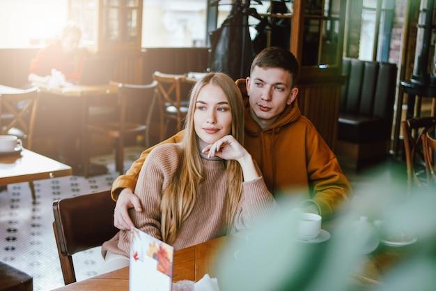 若いカップルは一緒にカフェに座って暖かいカジュアルな服を着てください。 Premium写真
