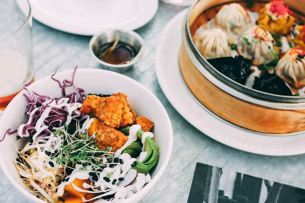 Паназиатская еда - овощная салатница и разные тусклые суммы в ресторане. обед на двоих с пивом Premium Фотографии
