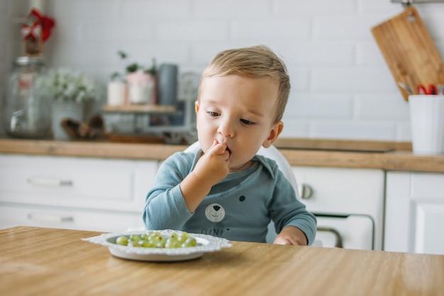 自宅の明るいキッチンでファーストフードグリーングレープを食べる魅力的な集中小さな男の子 Premium写真
