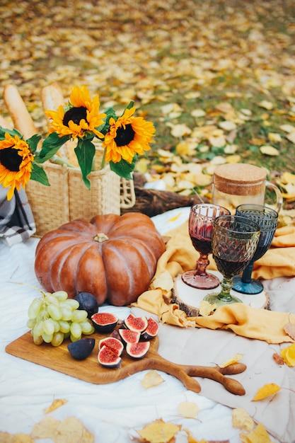 カボチャ、イチジク、ひまわりのある秋の静物。黄色の葉のピクニック Premium写真