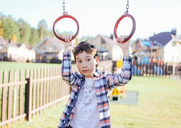 Вдумчивый тихий мальчик-подросток держит на кольцах на детской площадке, коттеджный поселок на фоне Premium Фотографии