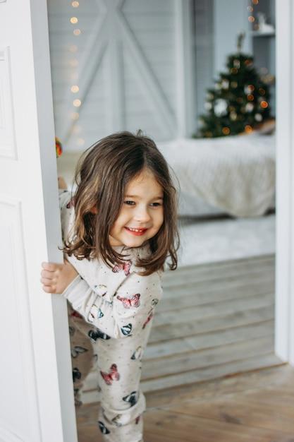 Маленькая счастливая брюнетка в уютной пижаме смотрит из детской комнаты, на рождество Premium Фотографии