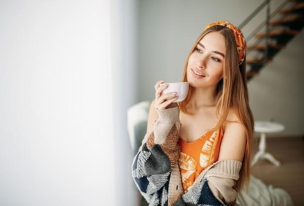 Красивая улыбающаяся девушка с длинными светлыми волосами в уютном вязаном кардигане с чашкой чая у окна Premium Фотографии