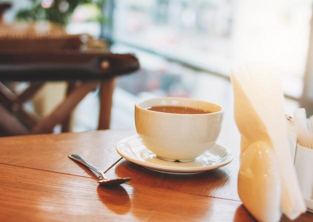 朝のウィンドウに対してカフェ木製テーブルの上のコーヒーカップ Premium写真
