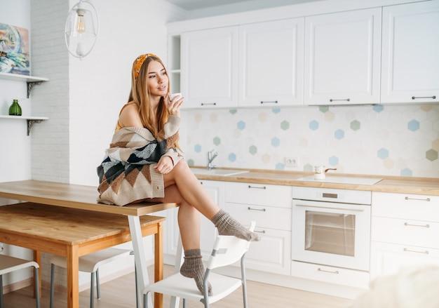 Красивая улыбающаяся девушка с длинными светлыми волосами в уютном вязаном кардигане с чашкой утреннего кофе сидит на кухонном столе дома Premium Фотографии