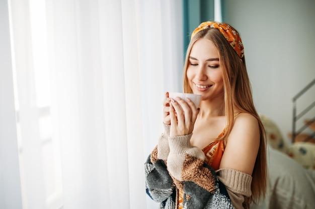 自宅の窓の近くのお茶と居心地の良いニットカーディガンを着て美しい笑顔の若い女性公正な長い髪の少女 Premium写真