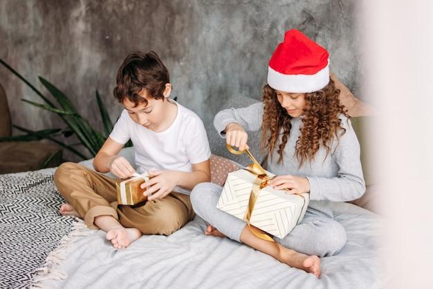 Симпатичные подростковые дети в шляпах и пижамах санта открывают рождественские подарочные коробки на кровати с подушкой, утренним рождественским праздником, детской вечеринкой Premium Фотографии