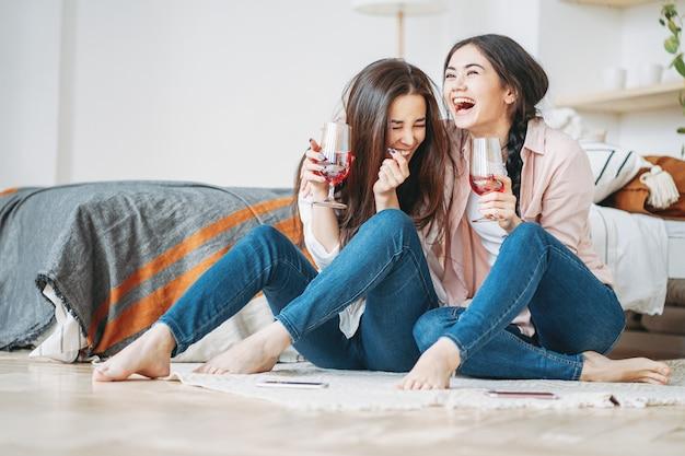 ホームパーティーで一緒に楽しんでワインのグラスとカジュアルな若い屈託のない笑いブルネットの女の子友達 Premium写真