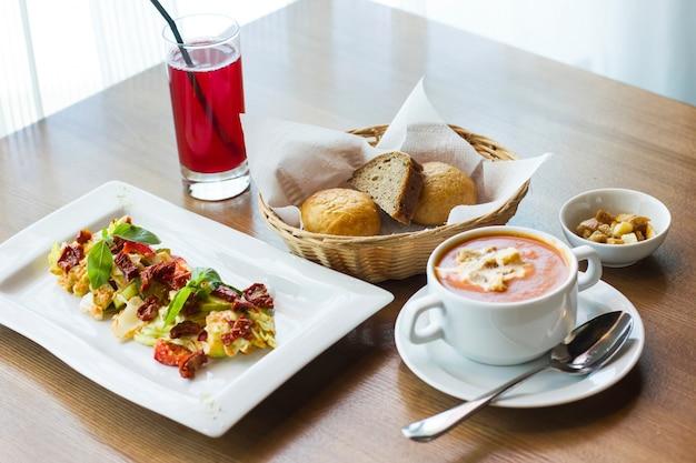 テーブルのランチ:トマトピューレスープ、新鮮な野菜のサラダ、太陽乾燥トマトとパン Premium写真