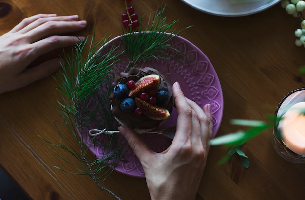 女の手はクリスマステーブルにイチジクと果実とカップケーキを持っています。上から見る Premium写真