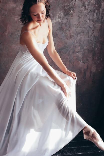 美しい薄い飛んで白いドレスのバレエダンサーバレリーナは暗いロフトスタジオでポーズをとっています。 Premium写真