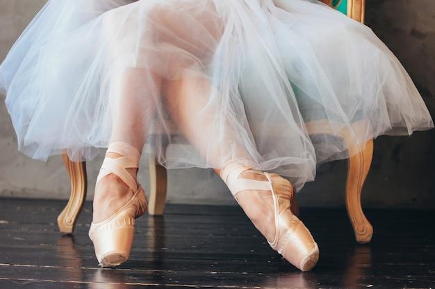 Балерина в балетной пачке и пуантах сидит на классическом стуле Premium Фотографии