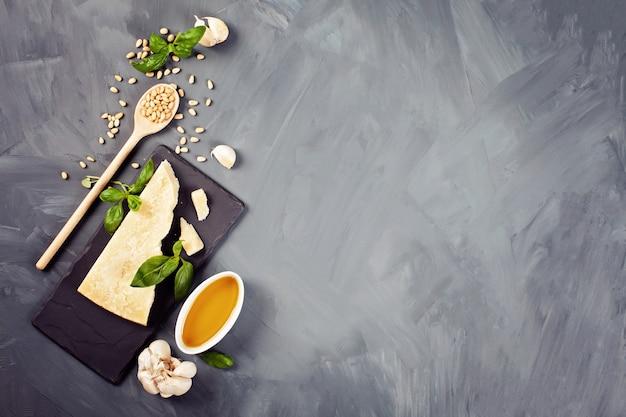 Сыр пармезан, оливковое масло, базилик, чеснок, кедровые орехи - свежие ингредиенты для приготовления песто. концепция итальянской кухни Premium Фотографии