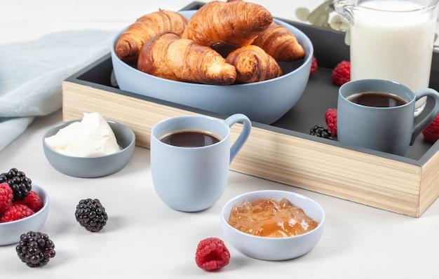 朝食はコーヒー、クロワッサン、新鮮なベリー、ミルク、クリーム、ジャムと一緒にお召し上がりいただけます Premium写真