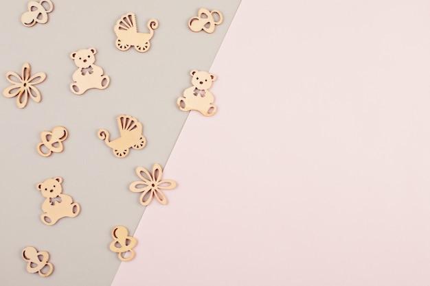 Минимальный пастельный декоративный фон с маленькими деревянными фигурками для новорожденного дня рождения Premium Фотографии