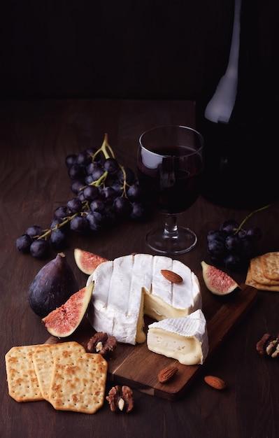 フランス産カマンベールチーズ、赤ワイン、ブドウ、イチジクのグラス Premium写真