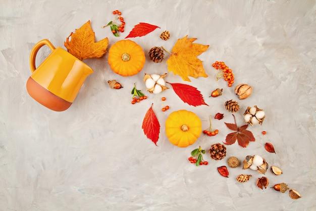 Осенние листья, тыквы, ягоды льются из кувшина на сером фоне Premium Фотографии