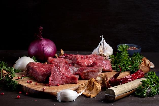 Сырое свежее мясо; бутылка вина и сезонные осенние органические овощи на деревянной доске готовы для приготовления пищи Premium Фотографии