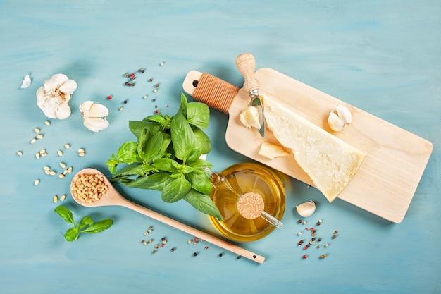 パルメザンチーズ、オリーブオイル、バジル、ニンニク、松の実-ペスト料理のレシピの新鮮な食材 Premium写真