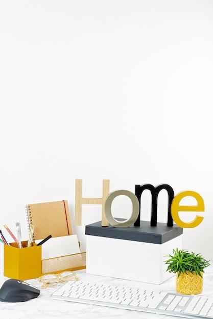 ポットとオフィス用品、コンピューターのキーボードとマウスの花を持つホームオフィスコンセプト Premium写真