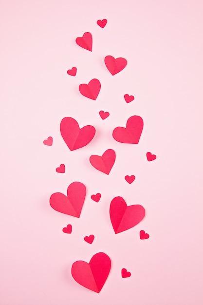 Бумажные сердца на розовом фоне пастельных. абстрактный фон с бумагой вырезать фигуры. день святого валентина, день матери, поздравительные открытки на день рождения, приглашение, концепция праздника Premium Фотографии