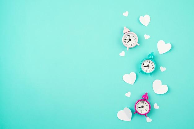 Белые бумажные сердца, будильники и облака на бирюзовом фоне. день святого валентина, день матери, поздравительные открытки на день рождения, приглашение, концепция праздника Premium Фотографии
