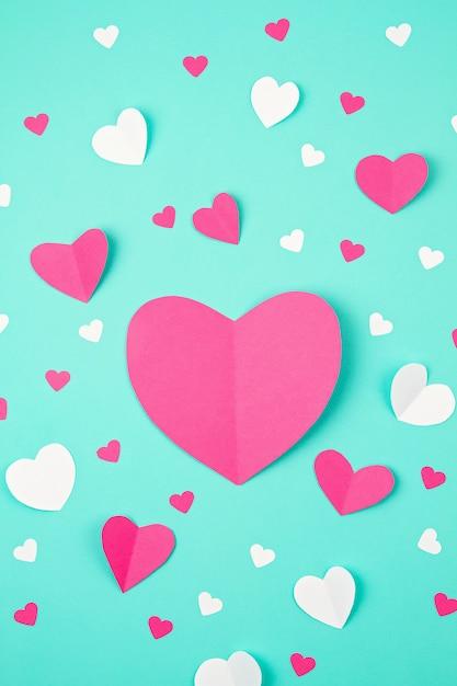 Розовые бумажные сердца на бирюзовом фоне. день святого валентина, день матери, поздравительные открытки на день рождения, приглашение, концепция праздника Premium Фотографии